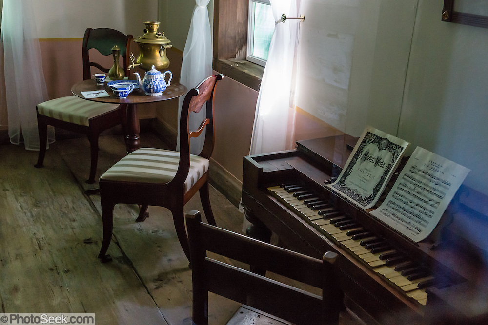 "At Fort Ross, the piano forte and exhibit furnishings in Rotchev House exactly copy the early 1800s originals and are set up to portray the late 1830s. Built circa 1836, Rotchev House is the only original remaining structure from Russia's thriving settlement in California. Fort Ross State Historic Park, which preserves a former Russian colony (1812-1842) on the west coast of North America, in what is now Sonoma County, California, USA. Visit Fort Ross and dramatic coastal scenery 11 miles north of Jenner on California Highway One.  Initially, sea otter pelts funded Russian expansion, but by 1820, overhunting motivated the Russian-American Company to introduce moratoriums on hunting seals and otters, the first marine-mammal conservation laws in the Pacific. Russian voyages greatly expanded California's scientific knowledge. For centuries before Europeans arrived, this site was called Metini and had been occupied by the Kashaya band of Pomo people who wove intricate baskets and harvested sea life, plants, acorns, deer, and small mammals. Sponsored by the Russian Empire, ""Settlement Ross"" was multicultural, built mostly by Alaskan Alutiiq natives and occupied mostly by native Siberians, Alaskans, Hawaiians, Californians, and mixed Europeans. Renamed ""Ross"" in 1812 in honor of Imperial Russian (Rossiia), Fortress Ross was intended to grow wheat and other crops to feed Russians living in Alaska, but after 30 years was found to be unsustainable. Fort Ross was sold to John Sutter in 1841, and his trusted assistant John Bidwell transported its hardware and animals to Sutter's Fort in the Sacramento Valley. Fort Ross is a landmark in European imperialism, which brought Spanish expanding west across the Atlantic Ocean and Russians spreading east across Siberia and the Pacific Ocean. In the early 1800s, Russians coming from the north met Spanish coming from the south along the Pacific Coast of California, followed by the USA arriving from the east in 1846 for the Mexican-Ameri"
