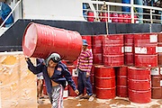 13 JUNE 2013 - YANGON, MYANMAR: Stevedores carry empty chemical drums off the Yangon docks. Yangon's docks and waterfront district is the heart of the Myanmar economy. Imports are brought in by ocean freighter and repacked onto river freighters for shipment within Myanmar while exports are brought to Yangon on river boats and then exported on ocean going cargo ships.    PHOTO BY JACK KURTZ