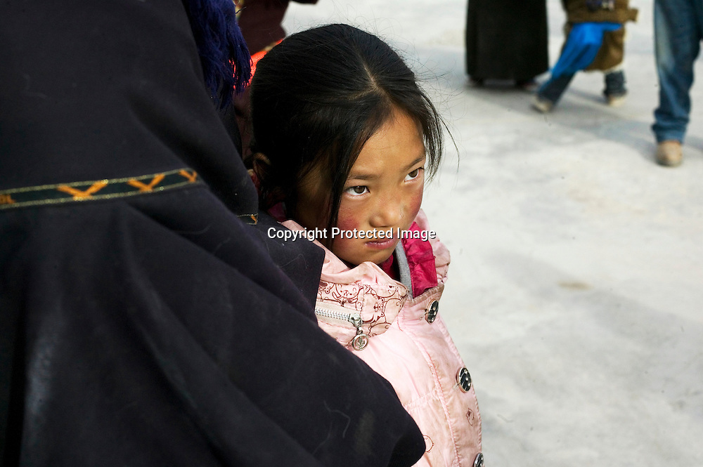 APRIL 5, 2012 : a Tibetan girl is protected by her mother at Lagrang monastery.