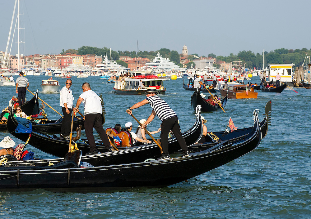 VENICE, ITALY - JULY 20: Gondoliers raw on a very busy stretch of the Grand Canal ahead of  the Redentore Celebrations on July 20, 2013 in Venice, Italy. Redentore , which is in remembrance of the end of the 1577 plague, is one of Venice's most loved celebrations. Highlights of the celebration include the pontoon bridge extending across the Giudecca Canal, gatherings on boats in the St. Mark's Basin and a spectacular fireworks display.  (Photo by Marco Secchi/Getty Images)