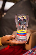 A pint glass with the image of President Hugo Chávez in a street stall in Los Proceres, Caracas, Venezuela, 12th March 2013. During Hugo Chávez funeral many people and stand sold miscellaneous articles that perpetuate Chávez presence. Everything from T-shirts, badges, earrings, baseball caps, sun glasses seemed suitable to have the President's image. The cult of Chávez is now more alive than ever.