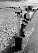 Young Boy looking through a Telescope with a Wet Paint Sign, Caister on Sea, Norfolk, England.