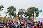 Bicycle stuntman a crowd of people watching below