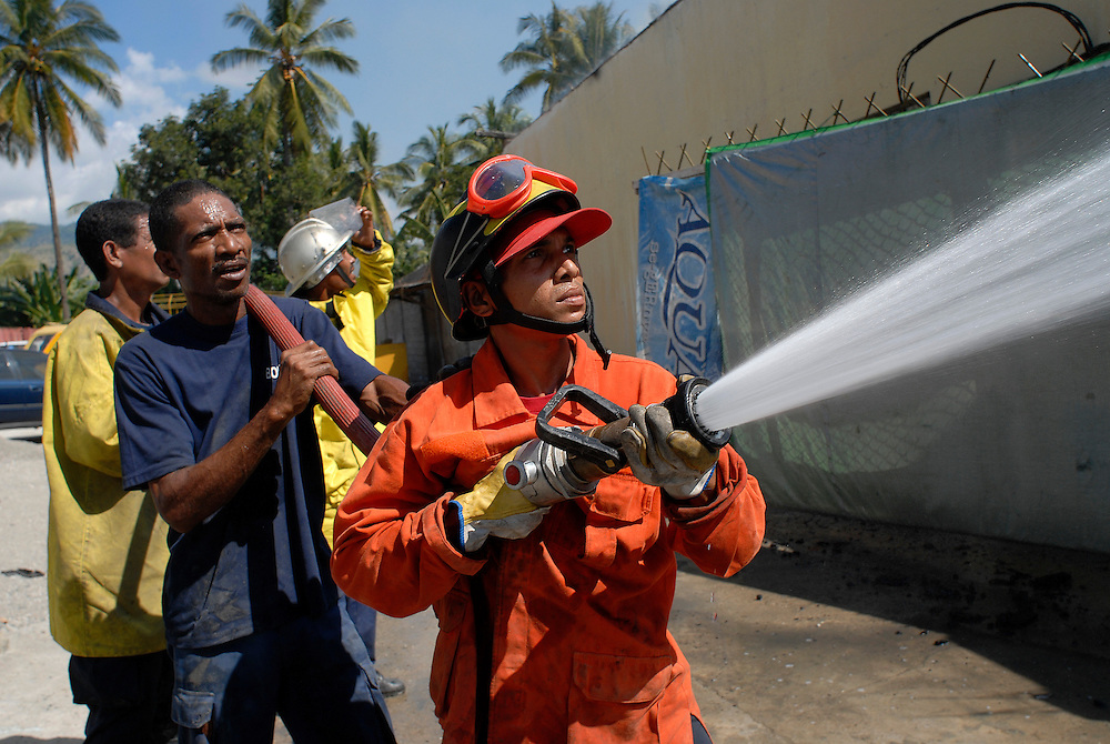 East Timorese firefighters, the Bombeiros, attempt to put out a major fire lit by fueding gangs. Acts of arson across Dili have become a continual occurence. 030606