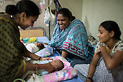 Manisha (center) and Nita (right), both ex-surrogates, have continued to work with Dr. Patel's Akanksha clinic as a nannies for new-born test tube babies, like these twins in the Neonatal Intensive Care Unit (NICU) at the Apara Nursing Home, where babies from the Akanksha clnic are often sent for neonatal and other post-birth intensive care, in Anand, Gujarat, India on 10th December 2012. Manisha, a widow and mother of 3 of her own children, has taken care of over 100 babies for Dr Patel's surrogacy clients, making up to 15000 rupees per month. Photo by Suzanne Lee / Marie-Claire France
