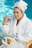 Young woman wearing bathrobe, drinking by swimming pool