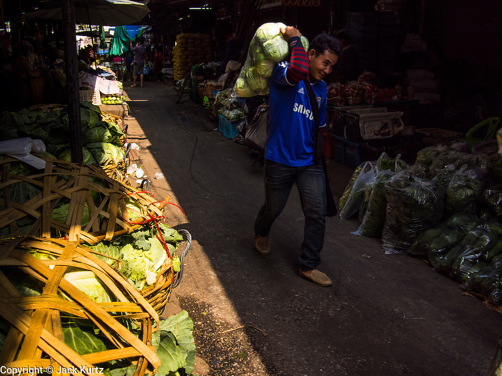 "19 DECEMBER 2013 - BANGKOK, THAILAND:  A man carries vegetables he bought through the flower market. Pak Khlong Talat (""the market at the mouth of the canal"") is a market in Bangkok that sells flowers, fruits, and vegetables. It is the primary flower market in Bangkok. It is located on Chak Phet Road and adjacent side-streets, close to Memorial Bridge. The market is open 24 hours, but is busiest before dawn, when boats and trucks arrive with flowers from nearby provinces.      PHOTO BY JACK KURTZ"