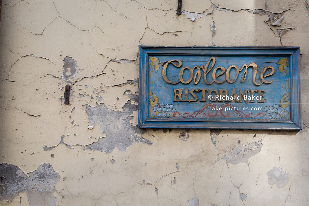 A detail of a peeling wall and a nameplate for the Ristorante Corleone on Poselska street in central Krakow, on 23rd September 2019, in Krakow, Malopolska, Poland.
