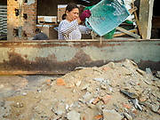 "14 FEBRUARY 2019 - SIHANOUKVILLE, CAMBODIA:  A Cambodian woman puts construction debris into the bed of a truck on the site of a Chinese hotel being built in Sihanoukville. There are about 80 Chinese casinos and resort hotels open in Sihanoukville and dozens more under construction. The casinos are changing the city, once a sleepy port on Southeast Asia's ""backpacker trail"" into a booming city. The change is coming with a cost though. Many Cambodian residents of Sihanoukville  have lost their homes to make way for the casinos and the jobs are going to Chinese workers, brought in to build casinos and work in the casinos.    PHOTO BY JACK KURTZ"