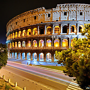 A shot of Rome's famous and historic Coliseum at night, with the lights of passing traffic blurred above the road.