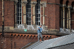 © Licensed to London News Pictures . 15/09/2015 . Manchester , UK . STUART HORNER throws a strip of metal from the roof at HMP Manchester (formerly Strangeways Prison ), this morning (15th September 2015) . Photo credit : Joel Goodman/LNP