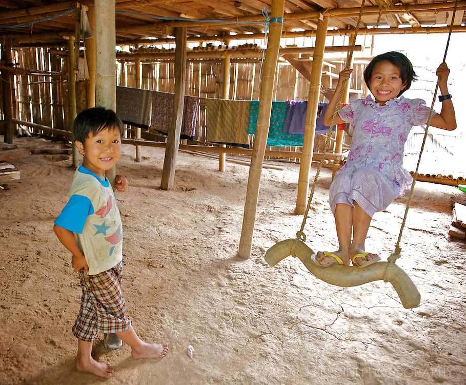 Two kids play with a swing in a bamboo hut close to their stilt house