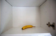 Empty kitchen cupboard with one banana