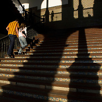 Couple walking up stairs in one of the buildings at the Plaza De España, Seville, Andalusia, Spain.