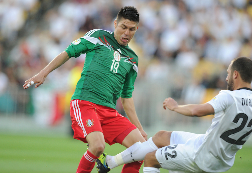 Mexico's Oribe Peralta, left, clashes with New Zealand's Andrew Durante in the World Cup Football qualifier, Westpac Stadium, Wellington, New Zealand, Wednesday, November 20, 2013.  Credit:SNPA / Ross Setford