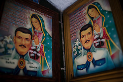 A picture of Jesus Malverde and the Vrigin of Guadalupe hangs in Culiacan, Mexico.  Malverde is a folk saint worshipped by many people in the underworld and often associated with narcoculture and drug dealers. He is thought of as the Mexican version of Robin Hood, looking after those who have been forgotten by the Church and are involved in a life of crime.  People come to the chapel to show their respect and pray.