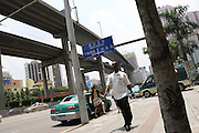 30 July 2007 - Guangzhou, China - An African man walks down the street in central Guangzhou. By some estimates over 10,000 Africans from many different nations live and pass through Guangzhou which has overtaken Hong Kong as the new hub for African businessmen looking to cut out the middle man. Some come for a few weeks, others years. These African traders, most of whom come from West African nations like Ghana, Togo and Nigeria, profit by purchasing cheap goods direct from Chinese factories and then sending them back to their home countries where they can be sold at higher prices. Photo Credit: Luke Duggleby