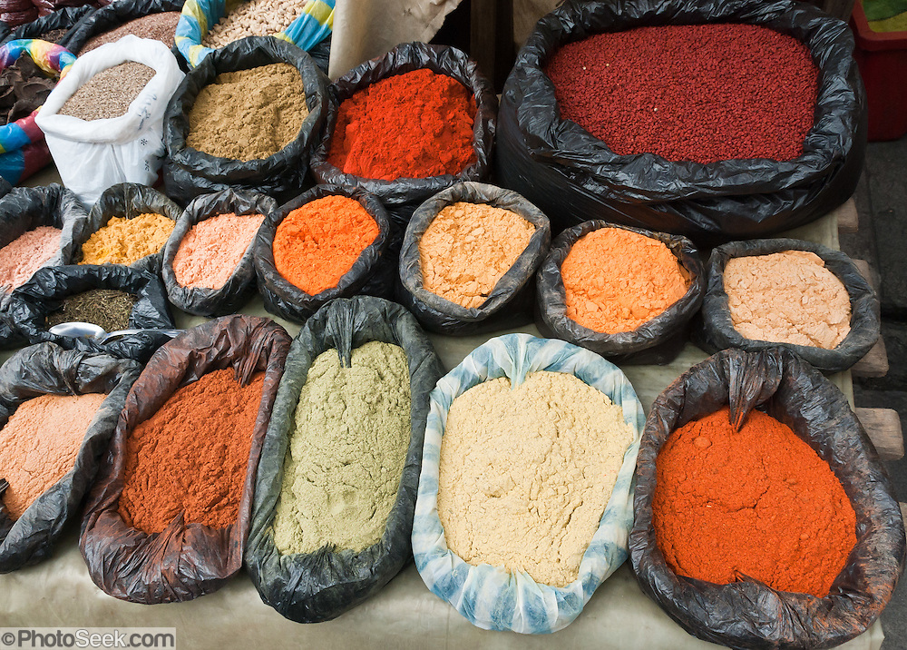 Colorful spices are sold in the Otavalo food market. The culturally vibrant town of Otavalo attracts many tourists to a valley of the Imbabura Province of Ecuador, surrounded by the peaks of Imbabura 4,610m, Cotacachi 4,995m, and Mojanda volcanoes. The indigenous Otavaleños are famous for weaving textiles, usually made of wool, which are sold at the famous Saturday market and smaller markets during the rest of the week. The Plaza del Ponchos and many shops tantalize buyers with a wide array of handicrafts. Nearby villages and towns are also famous for particular crafts: Cotacachi, the center of Ecuador's leather industry, is known for its polished calf skins; and San Antonio specializes in wood carving of statues, picture frames and furniture. Otavaliña women traditionally wear distinctive white embroidered blouses, with flared lace sleeves, and black or dark over skirts, with cream or white under skirts. Long hair is tied back with a 3cm band of woven multi colored material, often matching the band which is wound several times around their waists. They usually have many strings of gold beads around their necks, and matching tightly wound long strings of coral beads around each wrist. Men wear white trousers, and dark blue ponchos. Otavalo is also known for its Inca-influenced traditional music (sometimes known as Andean New Age) and musicians who travel around the world.