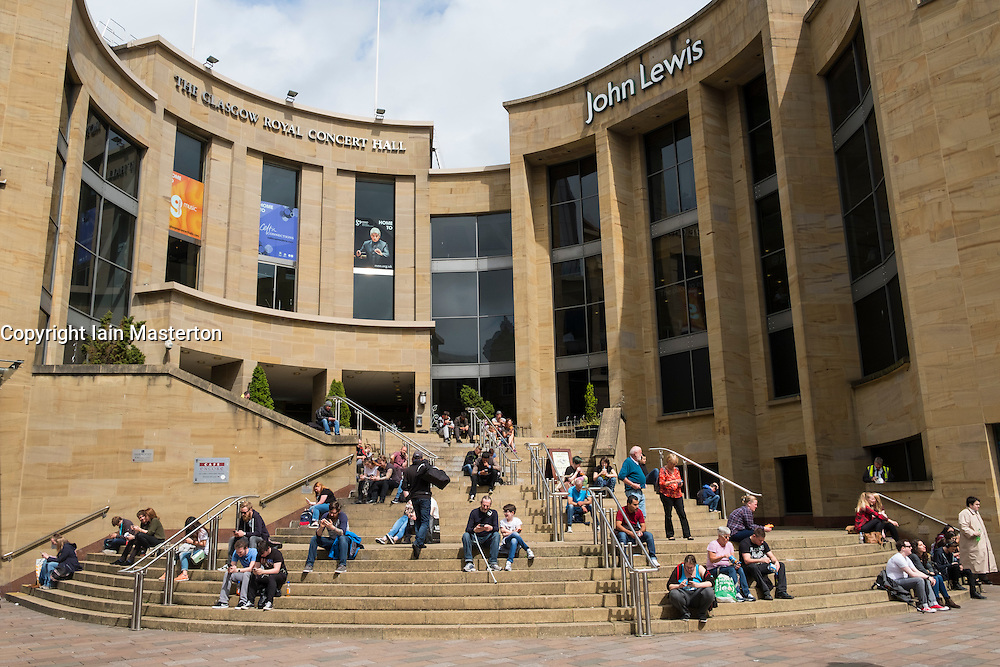 People sitting outside in the sun on steps of Glasgow Royal Concert Hall in Glasgow, Scotland, united Kingdom