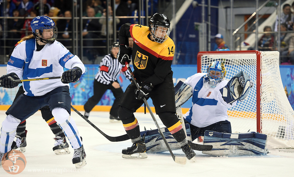 Feb 16, 2014; Sochi, RUSSIA; Germany forward Jacqueline Janzen (14) screens a shot in front of Finland goalkeeper Noora Raty (right) in the women's ice hockey classifications round during the Sochi 2014 Olympic Winter Games at Shayba Arena.