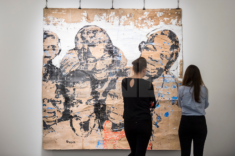 "© Licensed to London News Pictures. 29/03/2019. LONDON, UK. Staff members view ""Les bras Môgô du ghetto 2"", by Armand Boua (Est. GBP 4,000-6,000). Preview of Sotheby's upcoming Modern and Contemporary African Art sale.  Works from artists across the African diaspora will be offered for sale on 2 April.  Photo credit: Stephen Chung/LNP"