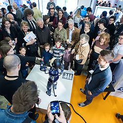 Lyon, France - 19 March 2014: a crowd gathers and plays with iCub by the Italian Istitute of Technology at Innorobo 2014, the 4th international trade show on service robotics.