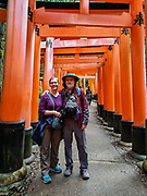 "Tourists posing. Fushimi Inari Shrine (Fushimi Inari Taisha) is an important Shinto shrine in southern Kyoto, Japan. Bright vermilion Senbon Torii (""thousands of torii gates"") straddle a network of trails behind its main buildings. The trails lead into the wooded forest of the sacred Mount Inari (233 meters). Fushimi Inari is the most important of several thousands of shrines dedicated to Inari, the Shinto god of rice. Foxes are thought to be Inari's messengers, honored in many statues. The shrine predates the capital's move to Kyoto in 794. The torii gates are donated by individuals and companies, as inscribed on the back of each gate. Prices for small to large gates run from 400,000 to over one million yen.  To license this Copyright photo, please inquire at PhotoSeek.com."
