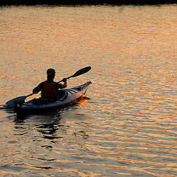 A woman kayaks at sunset in the Connecticut River in Old Lyme, Connecticut.