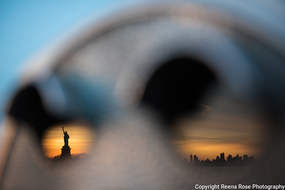 The silhouettes of the Statue of Liberty and the Brooklyn skyline are reflected on the lenses of a coin-operated telescope at Liberty State Park in Jersey City, N.J., at dawn.