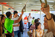 21 NOVEMBER 2012 - BANGKOK, THAILAND:  A passenger holds on while crossing the Chao Phraya River on a ferry. A network of ferries connect the Thonburi section of Bangkok to Bangkok proper, crossing the Chao Phraya River. The fare is 3 Thai Baht, about $ 0.15 (US). The boats are the fastest way to get from north to south in Bangkok. Thousands of people commute to work daily on the Chao Phraya Express Boats and fast boats that ply Khlong Saen Saeb. Boats are used to haul commodities through the city to deep water ports for export.   PHOTO BY JACK KURTZ