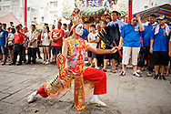 A dancer, said to be possessed by the spirit of a Taoist God, dances at a religious ceremony in Tainan, Taiwan.