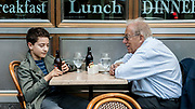 A young boy and an old man sit together at a cafe drinking Root Beer under window signage that is representative of their ages, breakfast and Dinner. Manhattan, New York