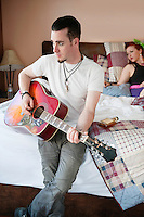 Man playing guitar while woman sitting on bed in background