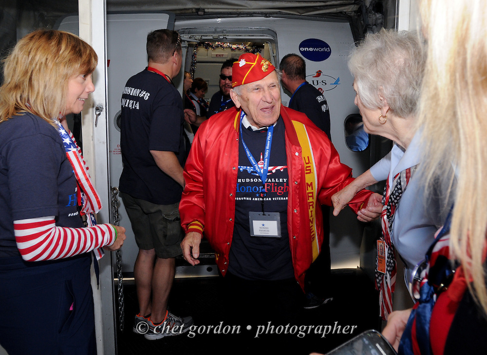 WWII Veteran Marine Nunzio Franchi (center) steps off a charter aircraft at Reagan National Airport in Arlington, VA on Saturday, October 18, 2014. Seventy-five WWII Veterans from the Westchester County area toured the WWII Memorial and Arlington National Cemetery onboard the inaugural flight from Westchester County Airport in White Plains, NY. Hudson Valley Honor Flight is a chapter of the Honor Flight Network, which provides free flights for WWII Veterans and tours of the WWII Memorial constructed in their honor, and other sites in the nation's capital.  © www.chetgordon.com