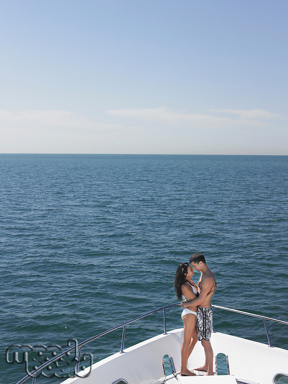 Young couple embracing on bow of yacht face to face side view