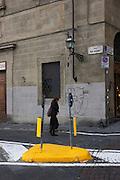 Woman passes road island in Florence's Via de Bardi on south bank of city, near Ponte Vecchio.