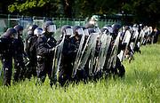 """Bad Doberan   June 6, 2007 . .Protest gegen den G8-Gipfel Heiligendamm, Tag 5: Heute gelingt es etwa 10000 Menschen, durch Strassenblockaden die Zufahrten zu dem umz?unten Sicherheitsbereich von Heiligendamm zu blockieren. An der Blockadestelle Pferderennbahn fanden sich etwa 4000 Menschen zusammen. Hier: Polizisten bewachen einen vorgelagerten Zaun an der Pferderennbahn...Protests against the G8-Summit Heiligendamm, Day 5: Today about 10000 people manage to block the roads to the Heiligendamm security aerea, about 4000 of them gather for the blockade at the checkpoint """"Pferderennbahn"""". Here: Riot policemen guard a first fence at the horse race track...[Inhaltsveraendernde Manipulation des Fotos nur nach ausdruecklicher Genehmigung des Fotografen. Vereinbarungen ueber Abtretung von Persoenlichkeitsrechten/Model Release der abgebildeten Person/Personen liegen nicht vor.]"""