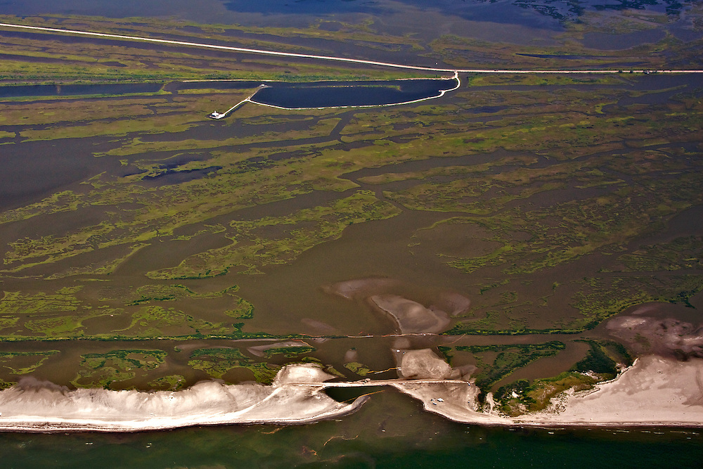 Sand berm and oil boom (bottom center) protecting wetlands, near Cheniere Caminada, Louisiana, USA. Note oil on beach and just offshore.