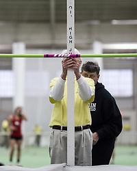 Bowdoin Indoor 4-way track meet: women's high jump, officials measure height of bar