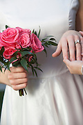 Bride holding bouquet and touching groom's hand, mid-section, close-up of hands