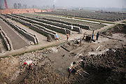 Workers mold bricks at JRB brick factory near Sonargaon, outside Dhaka, Bangladesh. The heavy clay soils along the river near the market town of Sonargaon are well suited for making bricks. At the JRB brick factory, workers of all ages move raw bricks from long, stacked rows, where they first dry in the sun, to the smoky coal-fired kilns. After being fired, the bricks turn red. A foreman keeps tally, handing the workers colored plastic tokens corresponding to the number of bricks they carry past him. They cash in the chips at the end of each shift, taking home the equivalent of $2 to $4 (USD) a day.