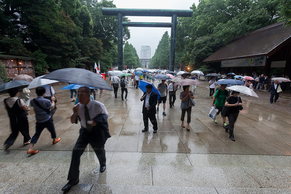 People using umbrellas approach Yasukuni shrine under a large Torii gate as Yasukuni shrine marks the 72nd anniversary of the end of the Pacific War. Yasukuni Shrine, Kudanshita, Tokyo Japan. Tuesday August 15th 2017. Nominally a event to honour Japan's war dead and call for continued peace, this annual gathering  at Tokyo's controversial Yasukuni  Shine also allows many Japanese nationalists to display their nostalgia for their Imperial past.Rightwing paramilitary groups, Imperial cos-players, politicians and many ordinary citizens come together at the shrine to march and wave flags. The day goes almost unreported in the mainstream Japanese media.