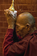 Myanmar/Burma, Mandalay. A monk is praying and holding an image of a stupa in his hands.