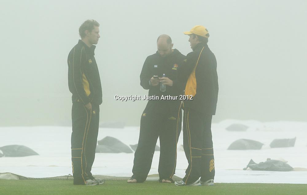 Players stand in the fog. Plunket Shield Cricket - Wellington v Northen Districts ,Karori Park, Wellington, New Zealand on Tuesday 18 December 2012. Photo: Justin Arthur / photosport.co.nz