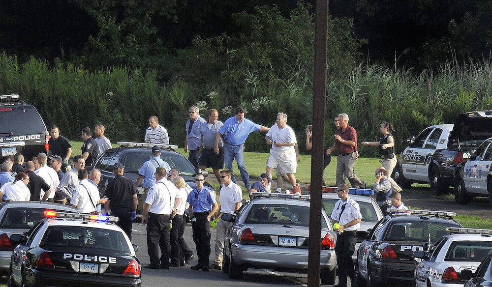 People are seen being evacuated from Hartford Distributors in Manchester, Conn., Tuesday, Aug. 3, 2010. A warehouse worker opened fire at the beer distributor killing seven wounding others. (AP Photo/Jessica Hill)