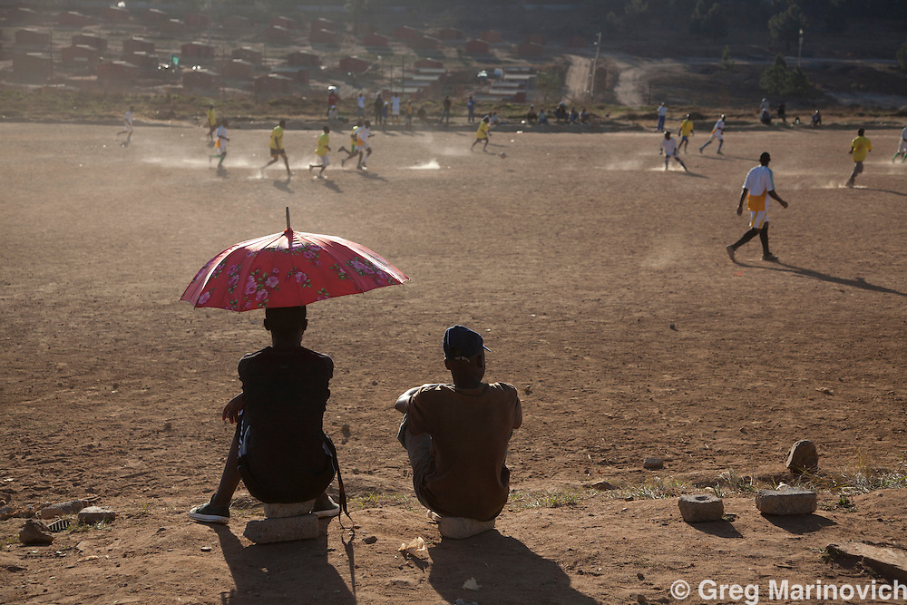 Children play netball and football (soccer) on dusty fields in, Cosmo City, Johannesburg North. Cosmo City is an idealistic project community where bought (mortgage) home neighbourhoods were built alongside free state housing (RDP houses) to try and break the usual ghetto-isation of of different socio-economic groups. Photo Greg Marinovich / StoryTaxi.com