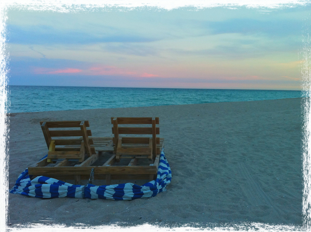two lounge chairs on a sunset beach