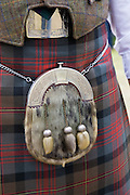 A fur Sporran hangs by a chain round the waist of a man wearing a woollen tartan kilt, in Rockness, Scotland. The kilt is a knee-length garment with pleats at the rear, originating in the traditional dress of men and boys in the Scottish Highlands of the 16th century.