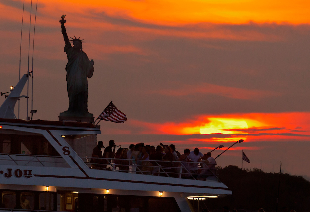 A summer Solstice party is going on, on this tour boat as they pass Lady Liberty.
