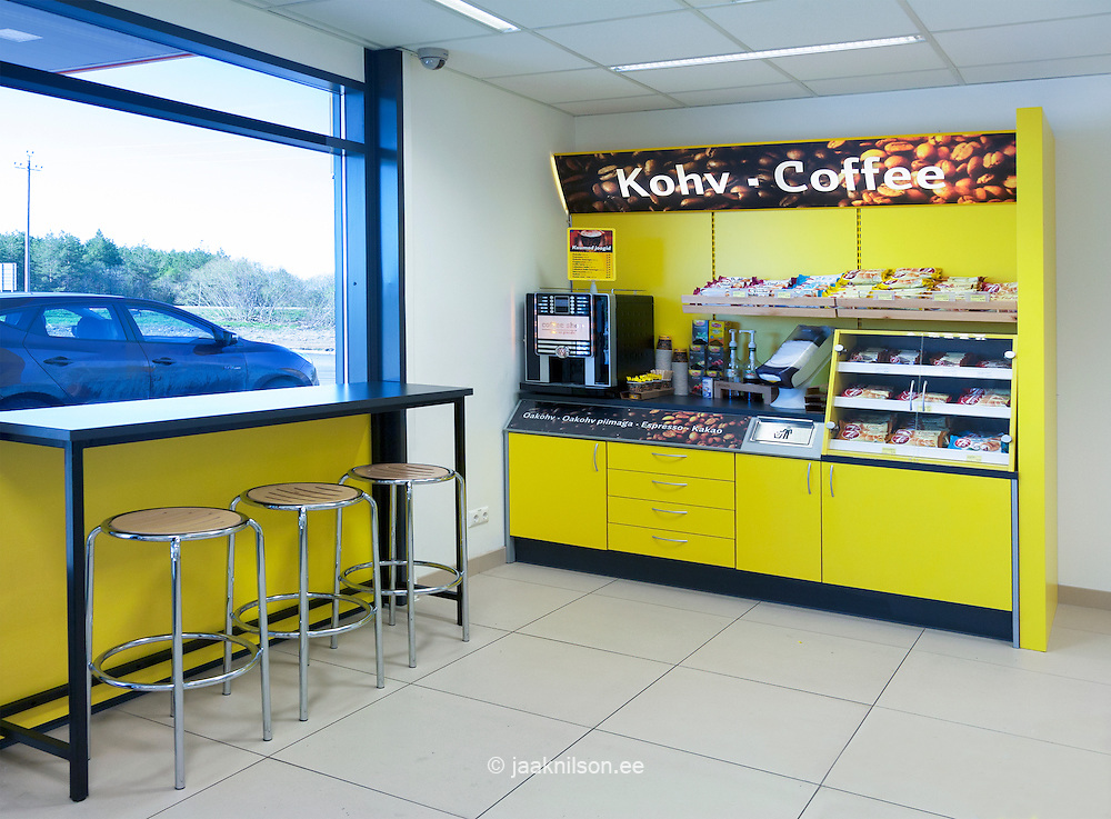 Gas station shop with coffee maker, shelves and food in Estonia. Window seat with table and chair. Coffee machine and fast food. Snacks. Furniture. Cafe, coffee-shop, self service.